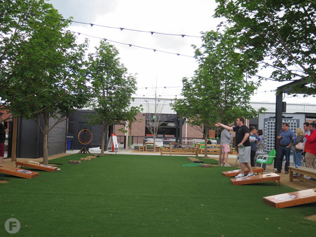 a group of people playing corn hole on the patio of Chicken N Pickle restaurant