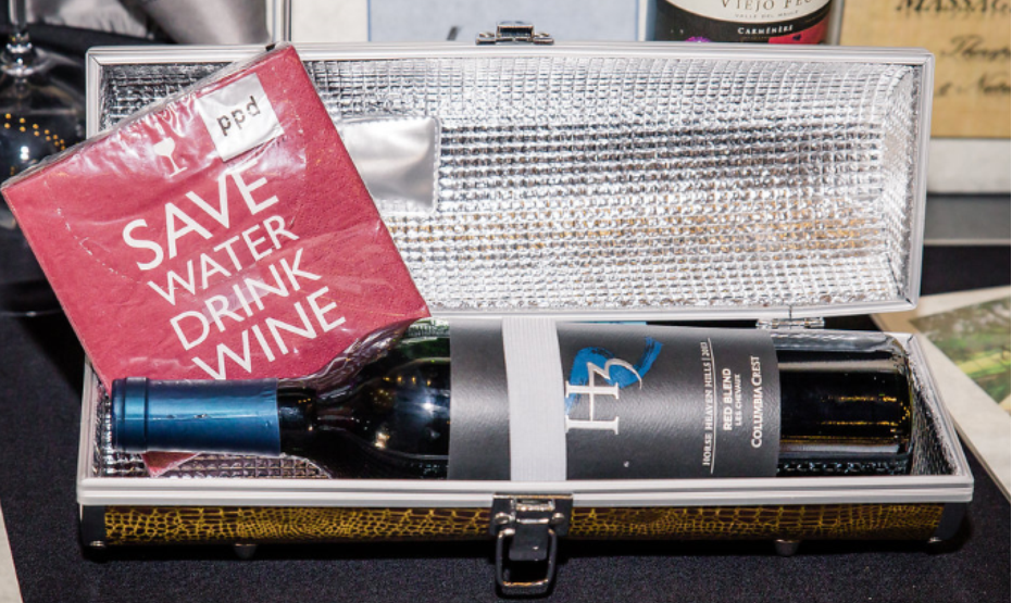 a bottle of wine in an opened case. There is a napkin that says Save Water; Drink Wine draped over the case