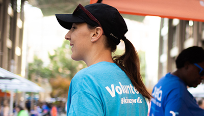 a woman wearing a baseball cap and a blue shirt with the word Volunteer printed on the back. She is volunteering at a Kidney Walk