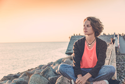 a woman sitting on a sea wall looking at the ocean