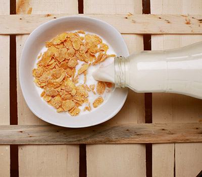 a bowl of corn flake cereal with milk