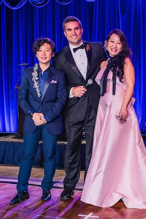 a group of four people standing together in formal dress at the Kidney Ball