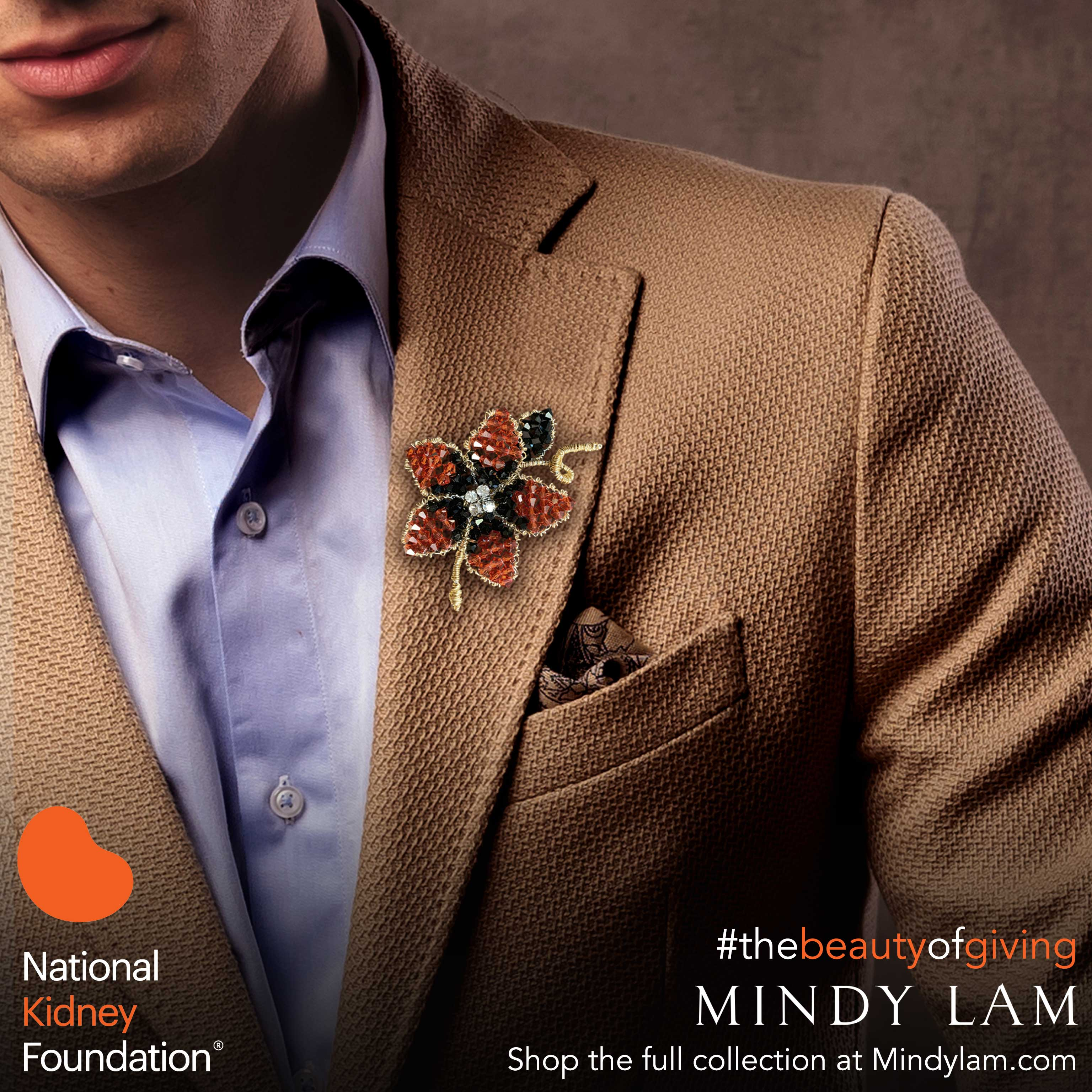 a closeup of the lapel of a brown suit showing a orange lapel pin designed by Mindy Lam
