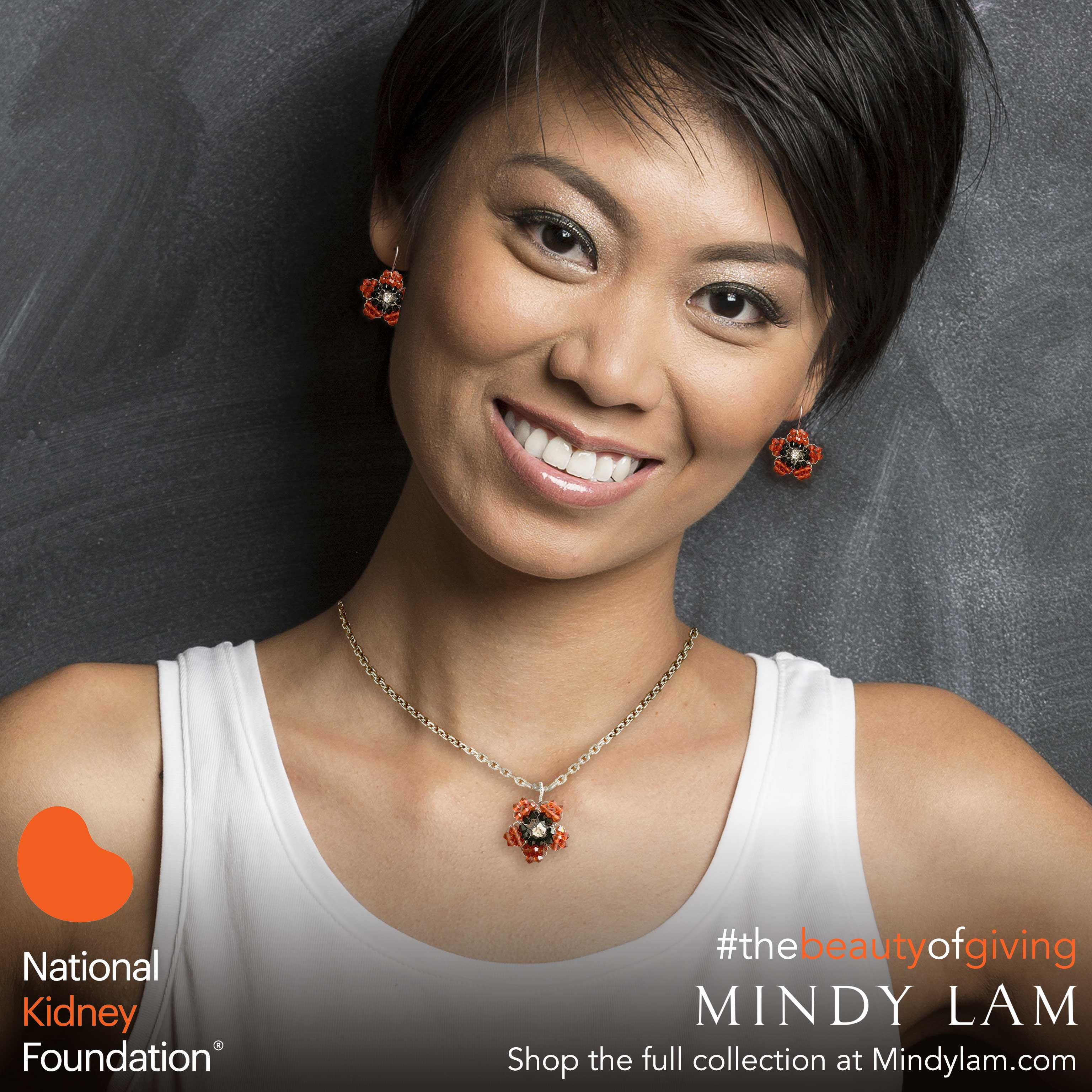 a woman with short dark hair and wearing a white tank top smiles at the camera, she is wearing a pair of orange earrings and an orange necklace designed by Mindy Lam