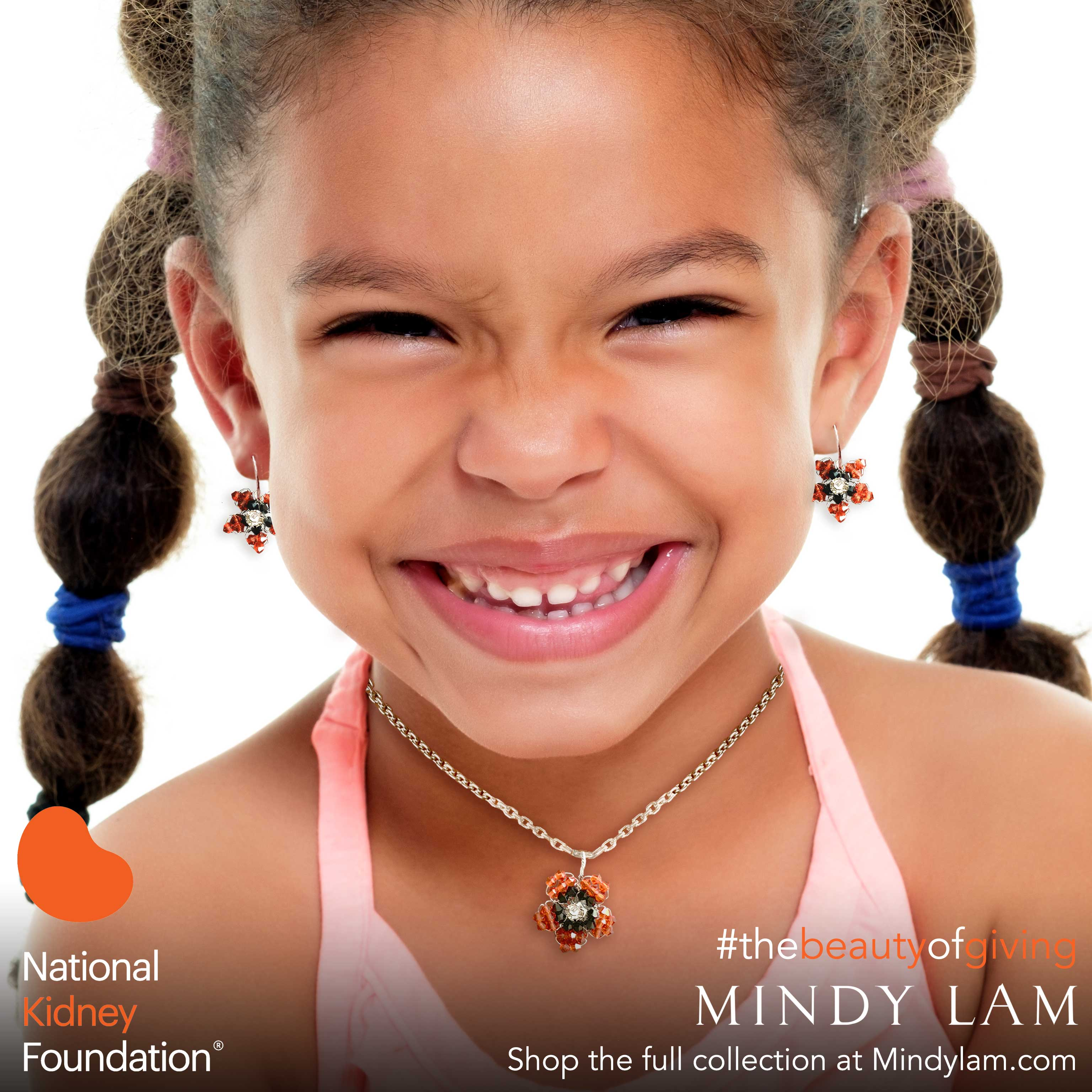 a young African American girl with a huge smile wearing a pair of orange earrings and an orange necklace designed by Mindy Lam