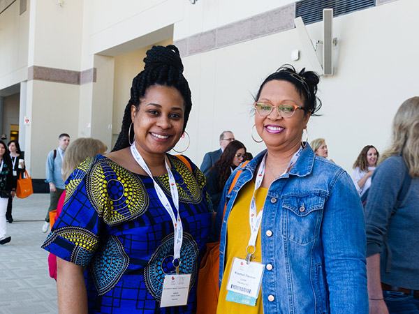 Two women smiling at a spring clinical meeting