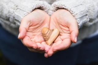 hand holding a wooden heart